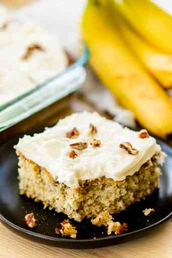 Piece of banana cake sits on a plate, garnished and ready to enjoy.