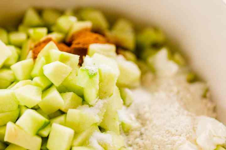 Cut apple slices sit in a bowl with other ingredients for he filling waiting to be mixed.