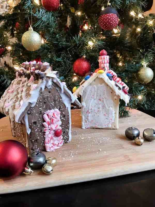 Two holiday houses are decorated with different candies sit in front of a lit Christmas tree.