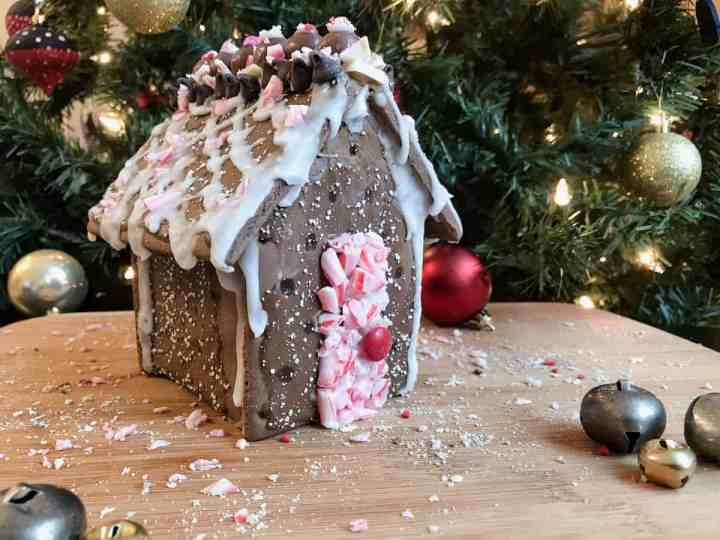 A chocolate holiday house is decorated with peppermint and sits in front of a lit Christmas tree.