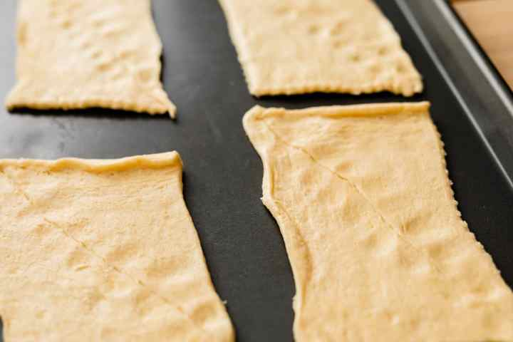 Crescent roll dough has been unrolled into four rectangular sections and the seams of each triangle pinched together.