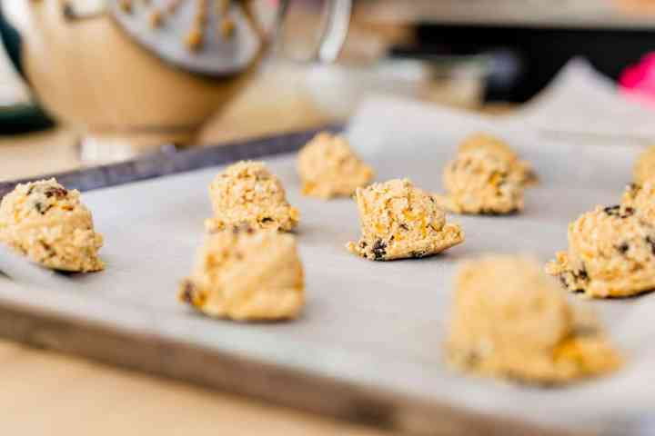 Balls of sunshine cookie dough are spaced on a cookie sheet ready to go into a hot oven to bake.