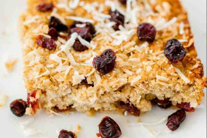 Large golden corner piece of baked oatmeal bars sits on a plate ready to enjoy.