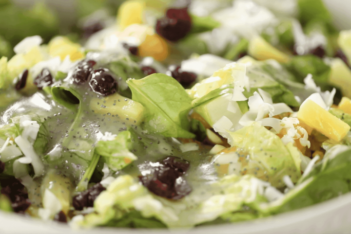 Poppy seed dressing is freshly poured on a fresh salad sprinkled with dried cranberries, swiss cheese, pineapples and mandarin orange wedges.