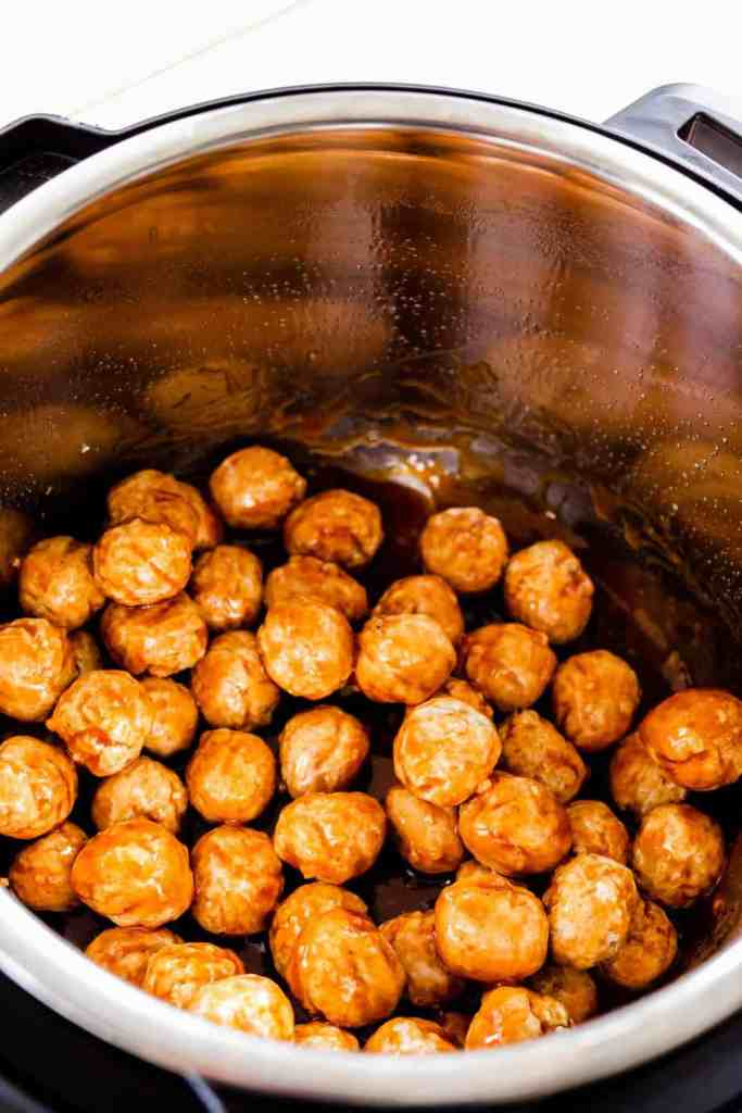 Meatballs are stirred in sauce to make sure they are covered.
