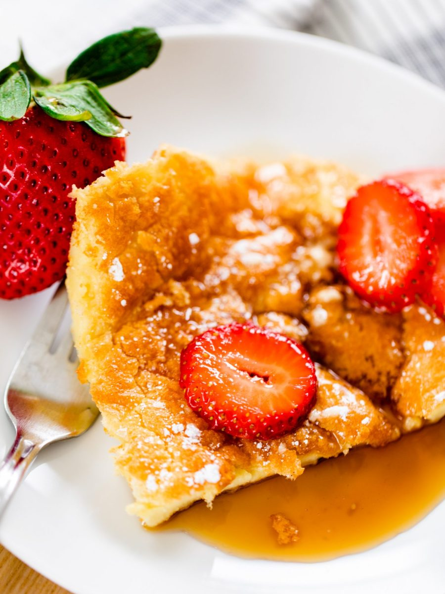 Slice of German Pancakes sit on a small round plate. Pancake is covered in caramel brown syrup and topped with sliced strawberries.