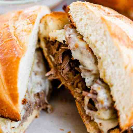 A shredded beef sandwich has been cut in half ready to be dipped in the bowl of au jus.