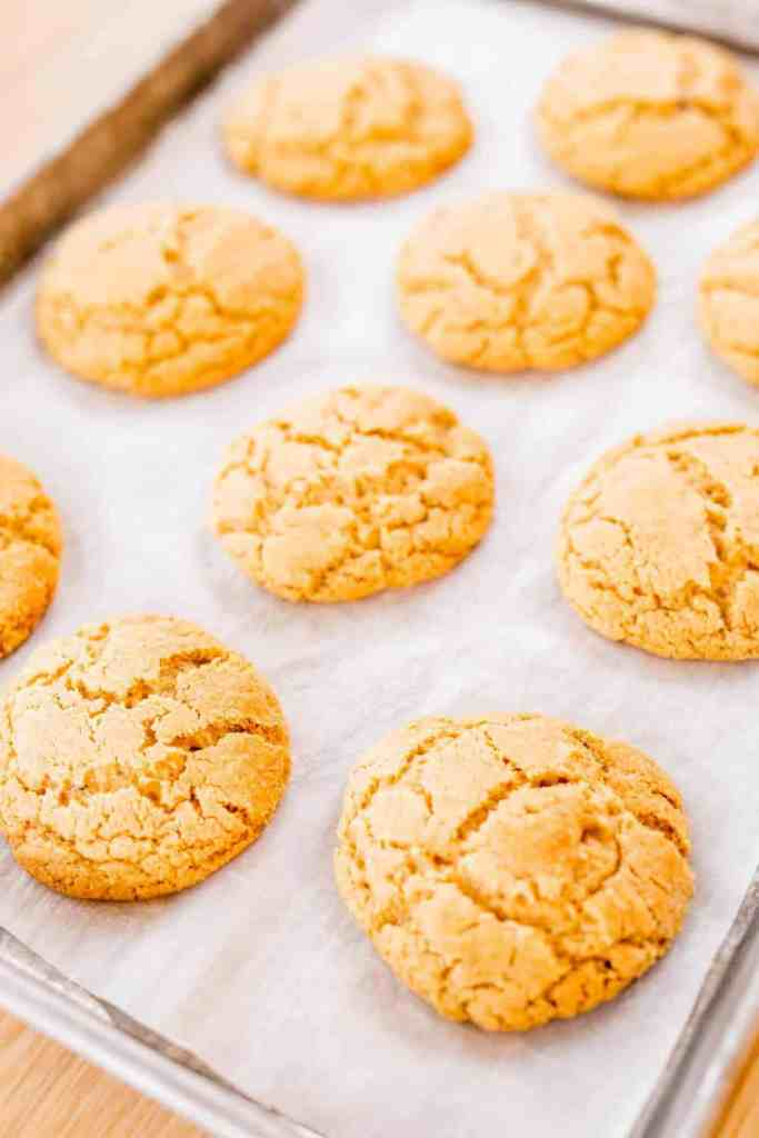 Perfectly baked peanut butter blossom cookies sit on a baking sheet ready for toppings.