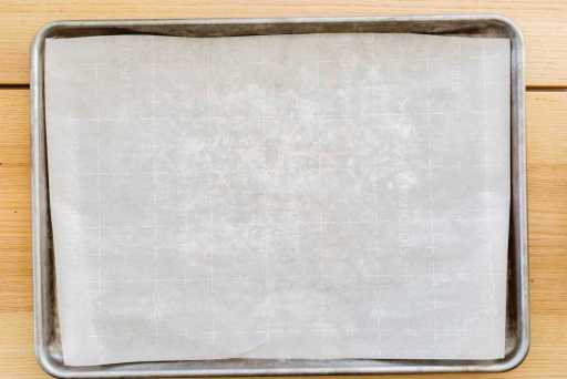 A baking sheet is lined with a piece of fresh parchment paper.