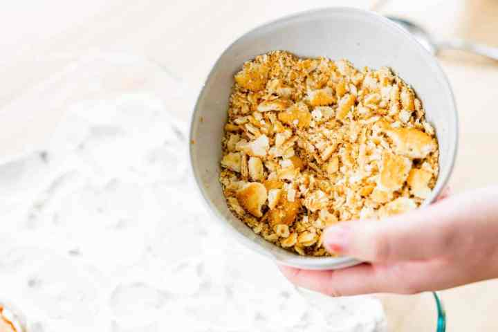 Crushed crackers in a bowl to be spread out over chicken in casserole dish.