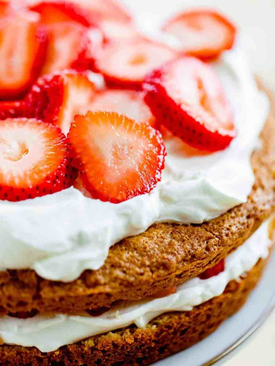Strawberry Layer Cake sits on counter topped with fresh sliced strawberries.