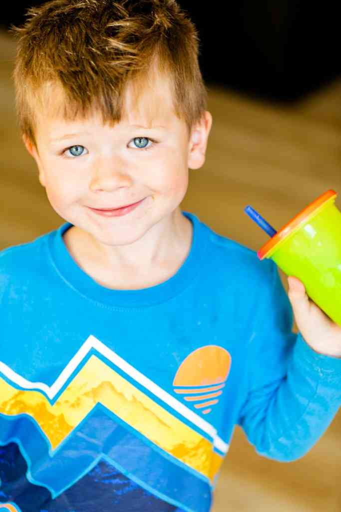 George is wearing a bright blue shirt and holding a cup with straw. His cup is filled with a bright green smoothie.
