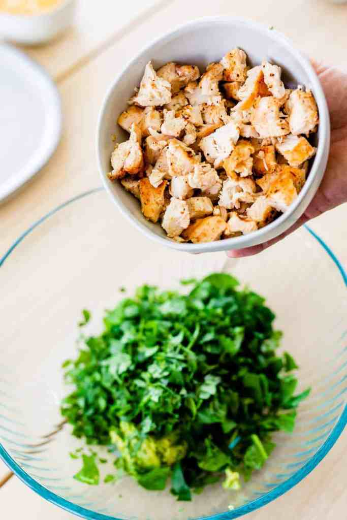 Grilled chicken is held in a small white bowl over the top of a bowl with cilantro and spinach.