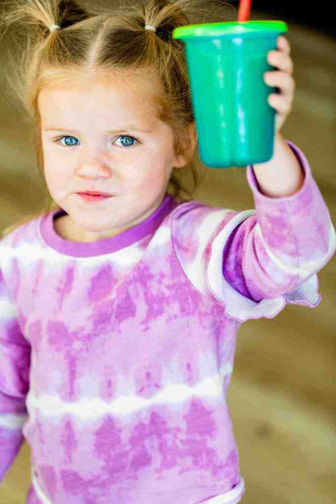 James is wearing a purple tie-dye shirt and holding a cup with straw. Her cup is filled with a bright green smoothie.