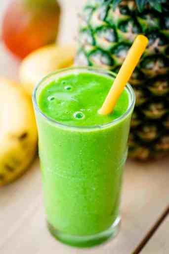 Vibrant green smoothie fills a tall glass cup. A yellow straw sits in the smoothie.