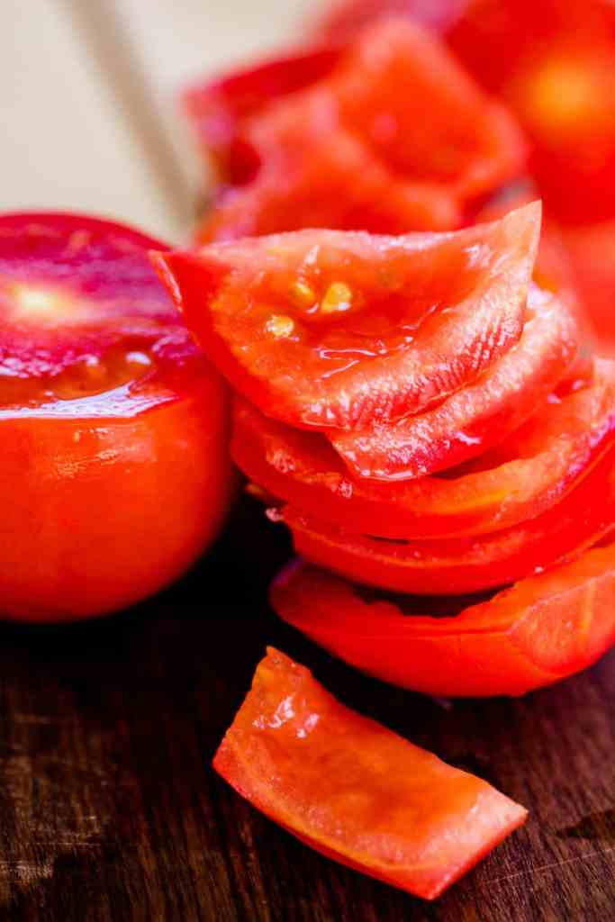 Quartered tomatoes sit on the counter in a stack, ready to be diced.
