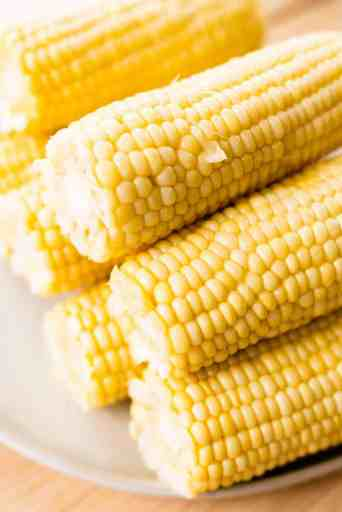 Cooked cobs of corn sit on a white plate, stacked in a pyramid.
