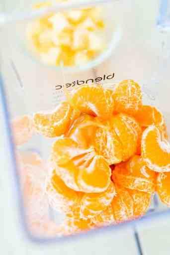 Open blender full of clementine oranges.