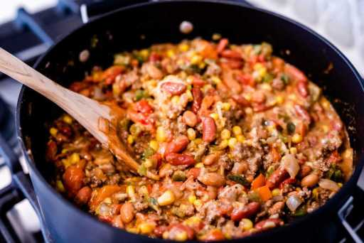 Tamale pie filling simmers in large black pot.