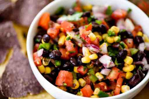 Bean and corn salsa sits in a serving bowl alongside blue corn chips.