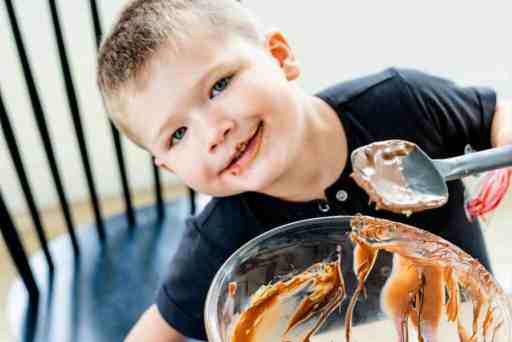 George sits at kitchen table with empty glass bowl with spatula in hand ready to clean off leftover chocolate topping.
