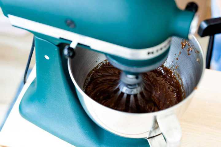 Kitchen Aid mixer is turned on and mixing chocolate cake batter.