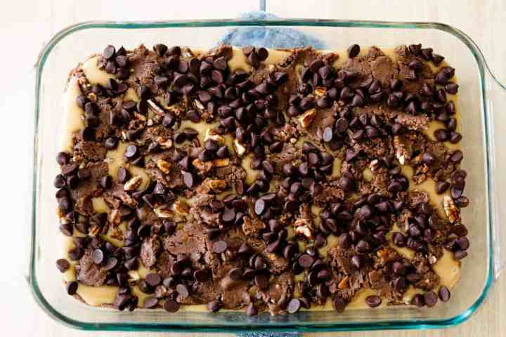 Chocolate chips are scattered across the top of the brownie dough, ready for the oven.