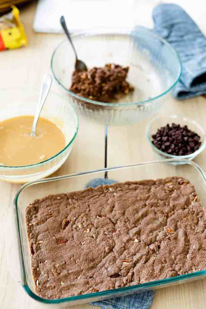 Bowl of caramel, chocolate chips and remaining brownie dough sit beside pan of baked brownie base layer.