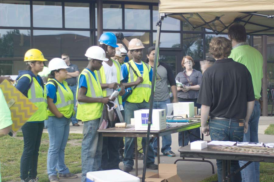 Workers in hard hats and bright vests standing at a table where someone is speaking to them