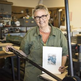 "Yellow Springs resident Sherraid Scott, at the Dayton Printmaking Cooperative on North Keowee Street, holds one of her prints, ""Song,"" for this year's 12th annual Dayton/Kyoto print exchange. The exhibit is displayed at the Dayton Visual Arts Center through Nov. 28, 2015. DOUG TAYLOR/CONTRIBUTED photo by: DOUG TAYLOR"
