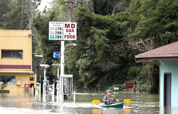 GUERNEVILLE, CA - JANUARY 11: A resident paddles his kayak through floodwaters in Guerneville. (Photo by Justin Sullivan/Getty Images)