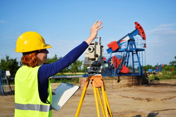 Female surveyor uses scope at oil-drilling site