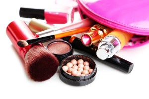 Used cosmetics are scattered from a makeup bag.