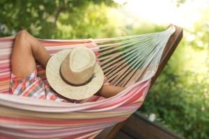 A man sleeps in a cloth hammock on a deck.