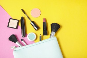 Cosmetic products spill out of a makeup bag.