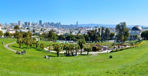 A sunny day at San Francisco's Dolores Park shows people relaxing in small groups.