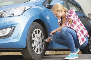 A woman uses a gauge to check her tire pressure.