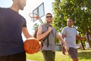 Three male friends chat on a basketball court.