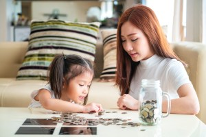 A mother and her daughter count coins on a coffee table.
