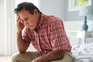 A depressed older man sits on the side of his bed.