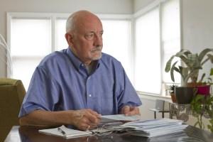 An older man worries over a pile of bills on his desk.
