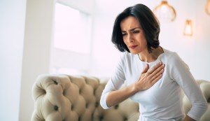 A woman in discomfort as she presses her hand to her chest.
