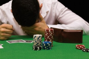 A man at a poker table holds his head in his hands.