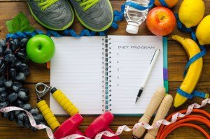 A fitness journal is surrounded by fresh fruit, sneakers, and exercise equipment.
