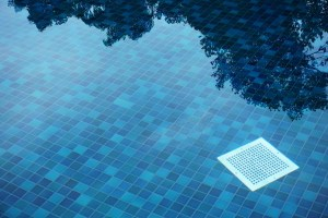 A flat drain cover at the bottom of a tiled pool.