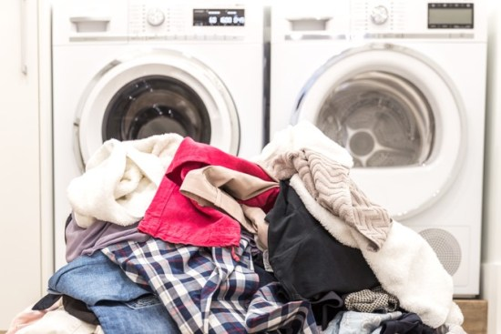 Pile of laundry in front of washing machines