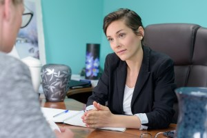 A female funeral director sitting at a desk listens attentively to a client.