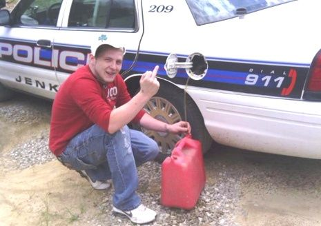 Man messing with a cop car's fuel tank.