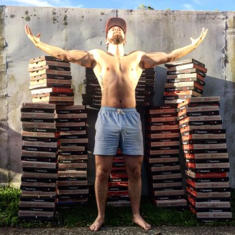 Proudly posing in front of 200 pizza boxes.