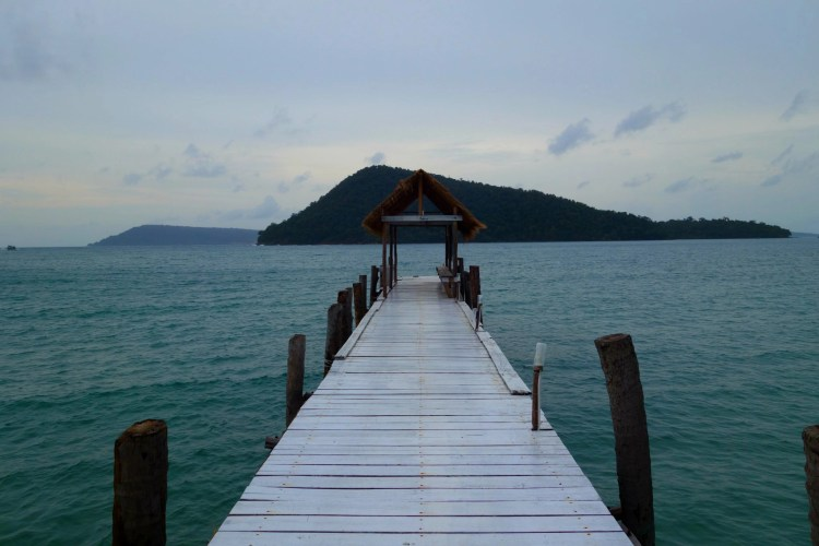An empty pier stretches into cool blue water on a blazing hot day.